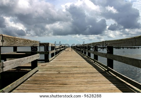 Wooden pier advancing into the darkening horizon - stock photo