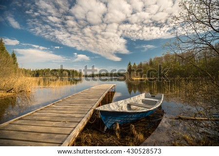 Wooden pier and boat on the lake. Beautiful landscape - stock photo