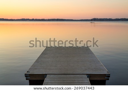 Wooden pier in the Scandinavian evening lake reflecting sunset colors - stock photo