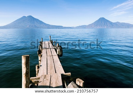 Wooden pier on the calm lake Atitlan in Guatemala with volcanoes in the distance - stock photo