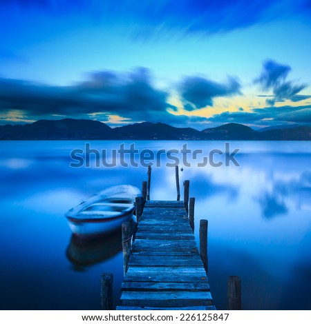 Wooden pier or jetty and a boat on lake sunset and sky reflection water. Long exposure, Versilia Massaciuccoli, Tuscany, Italy. - stock photo