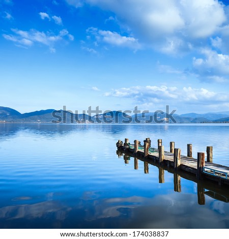 Wooden pier or jetty on a blue lake sunset and cloudy sky reflection on water. Long exposure, Versilia Massaciuccoli Lake, Tuscany, Italy. - stock photo
