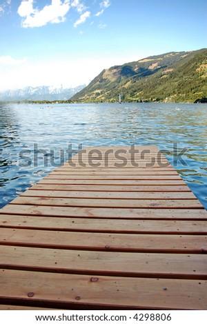 wooden pier over mountains lake - stock photo