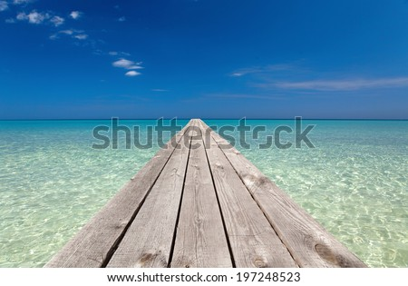wooden pier stretching into the ocean - stock photo