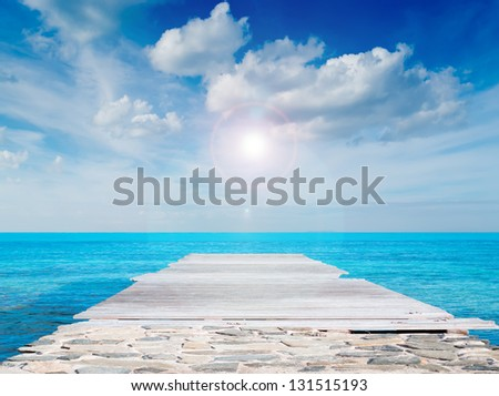 wooden pier under a cloudy sky - stock photo