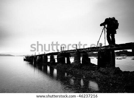wooden pier with explorer man , black and white - stock photo