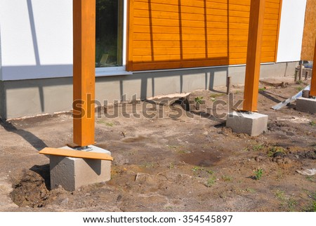 Wooden pillar on the construction site with screw and place for terrace. Wooden Pillars are structures that can be placed on Foundations or Platforms. - stock photo