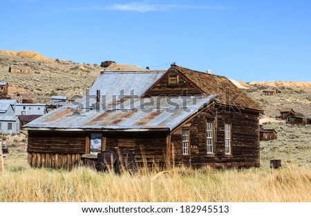 Wooden pioneer home now sits derelict and abandoned on a western prairie. - stock photo