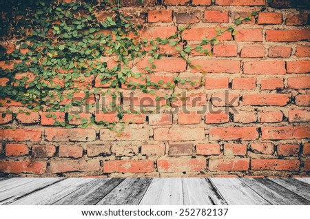 Wooden plank and leaves on brick wall  - stock photo