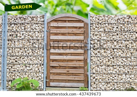 Wooden plank door with gabion wire garden fencing wall  from  steel mesh with stones,  Word GARDEN on Green arrow road direction pointer signs, green leaves plant, frame, text place, garden background - stock photo