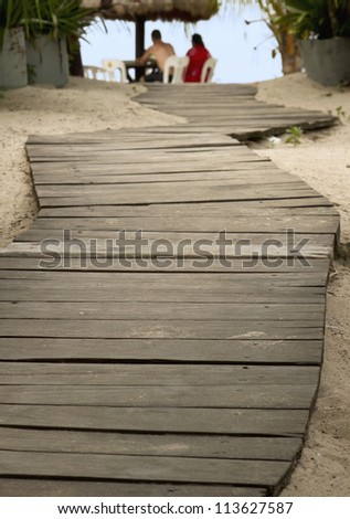 Wooden plank path leading to the beach shore. - stock photo