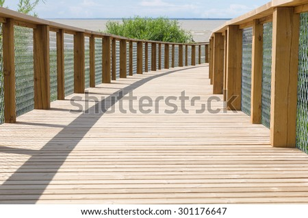 Wooden plank path with safety fence leading to the sea shore - stock photo