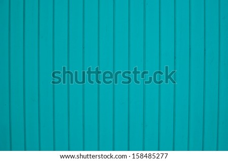 Wooden plank wall painted pretty turquoise colors.  Horizontal image with vertical stripes between wooden planks.  Can be used as background, texture or wallpaper and with copy space. - stock photo