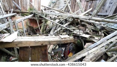 wooden planks and rubble and the ruins of the house completely destroyed by powerful earthquake - stock photo