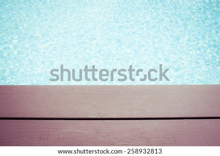 wooden planks at the pool side with vibrant pool water and a vintage effect - stock photo