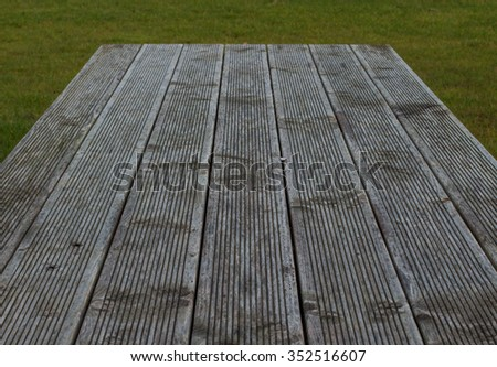 Wooden planks in front of a meadow. Created for placing text or objects - stock photo
