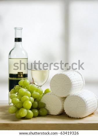 wooden plate of cheese grapes and wine - stock photo
