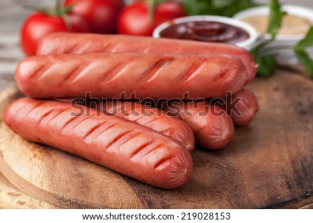 wooden Plate with hot sausages - stock photo