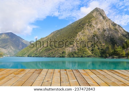 wooden platform before lake  with mountain - stock photo