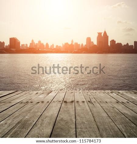 wooden platform before modern city - stock photo