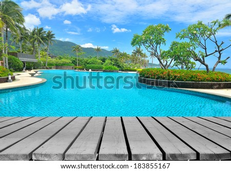 Wooden platform beside tropical resort hotel swimming pool  - stock photo