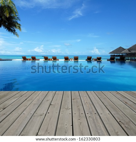 Wooden platform beside tropical resorts pool - stock photo