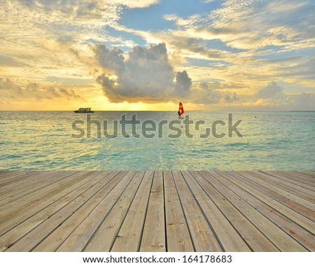 Wooden platform beside tropical sea with sunset - stock photo