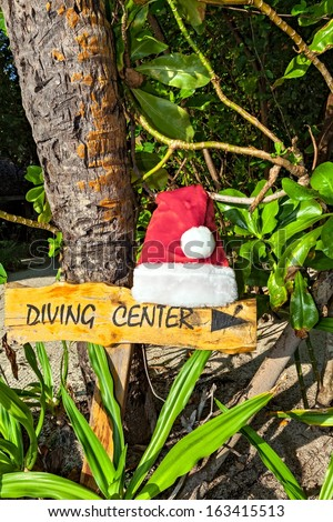 Wooden pointer to the diving center with cristmas hat on the  island Biyadhoo, Maldives, The Indian Ocean - stock photo