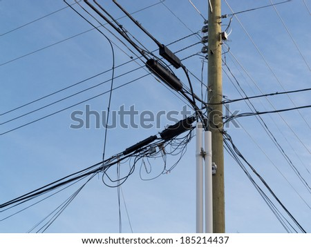 Wooden pole hung with confusing and messed-up electricity power cables and telephone lines for residential utilities supply - stock photo