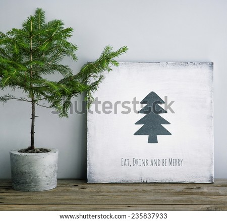 WOODEN POSTER EAT DRINK AND BE MERRY with  little christmas tree in diy concrete pot - stock photo
