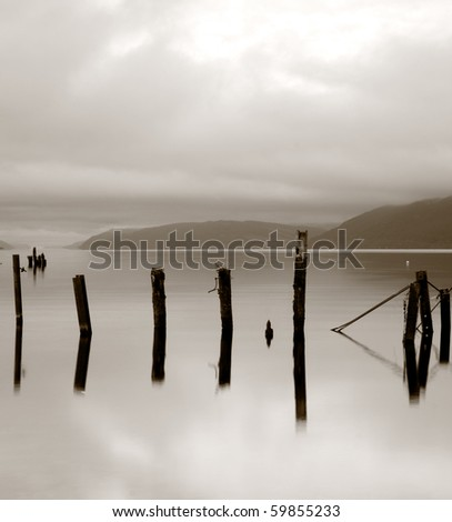 Wooden posts in lake. (Loch Ness, Scotland) - stock photo