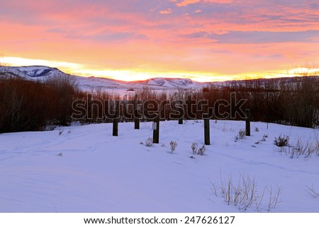 Wooden posts with a colorful sunrise, Utah, USA. - stock photo