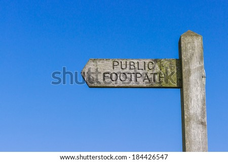 Wooden Public Footpath sign against a clear blue sky. - stock photo