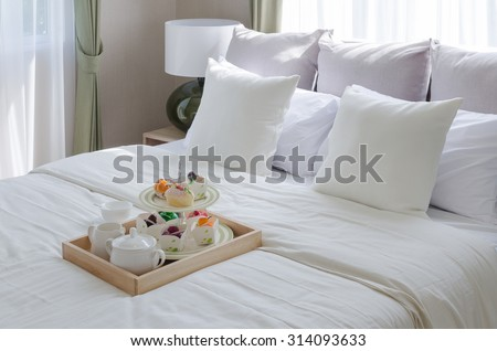 wooden ray of tea set and cup cake on white bed in modern bedroom - stock photo