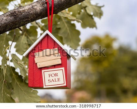 Wooden red birdhouse hanging on tree branch with entry hole covered with planks and note FOR SALE attached to it - stock photo