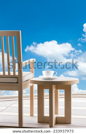 Wooden relax chairs and coffee cup with clouds in blue sky background. - stock photo
