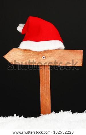 Wooden road sign with Santa hat black background - stock photo