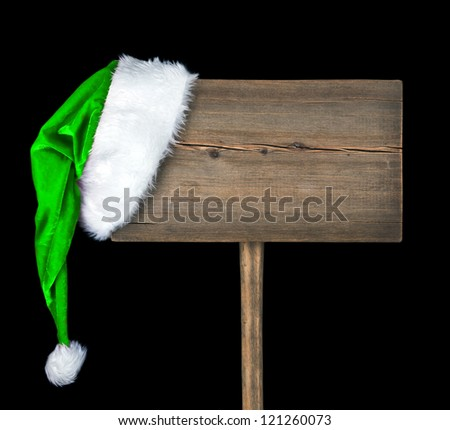 wooden road sign with Santa hat isolated on a black  background - stock photo