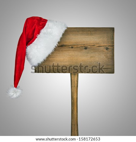 wooden road sign with Santa  hat isolated on a white background  - stock photo