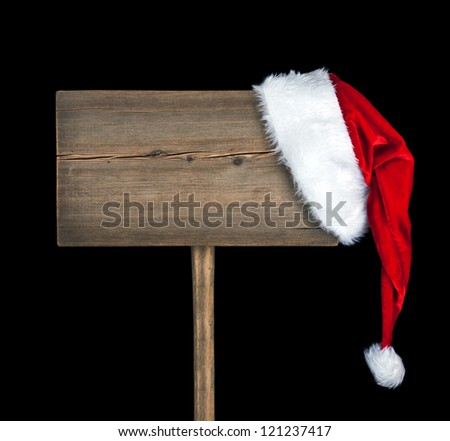 Wooden road sign with Santa hat isolated on black background - stock photo