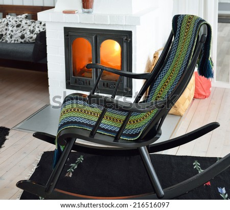 Wooden rocking chair in front of burning fireplace - stock photo
