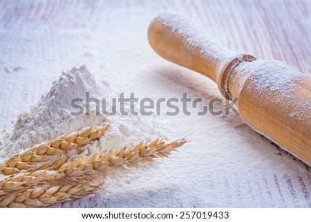 wooden rolling pin and heap flour with ears of  wheat on vintage board  - stock photo