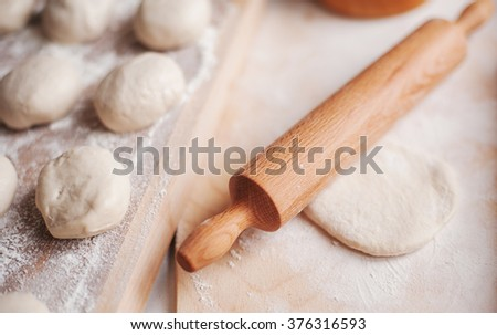 wooden rolling-pin and homemade dough ready for cooking pies - stock photo