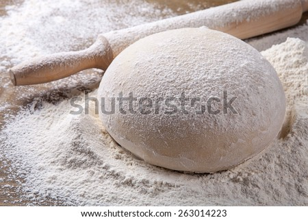 wooden rolling pin with dough and dusting of flour. - stock photo