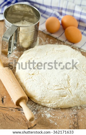 wooden rolling pin with freshly prepared dough - stock photo