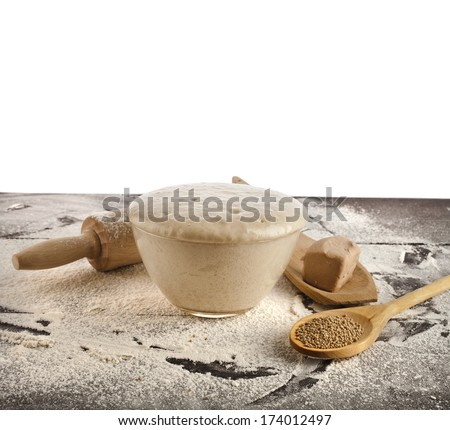 Wooden rolling pin with white wheat flour on the table isolated on white background  - stock photo