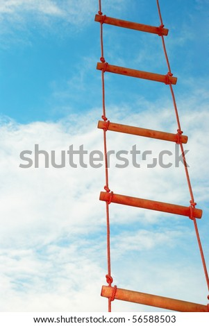 Wooden rope ladder on a blue sky background - stock photo