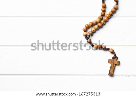 Wooden rosary beads on white wooden table - stock photo