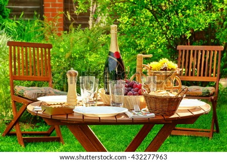Wooden Round Picnic Table With Bottle Of Wine and Plates On The Backyard, Concept For Outdoor Seasonal or Holiday Party or Picnic - stock photo