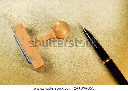 Wooden rubber stamp and inky pen on grungy background - stock photo